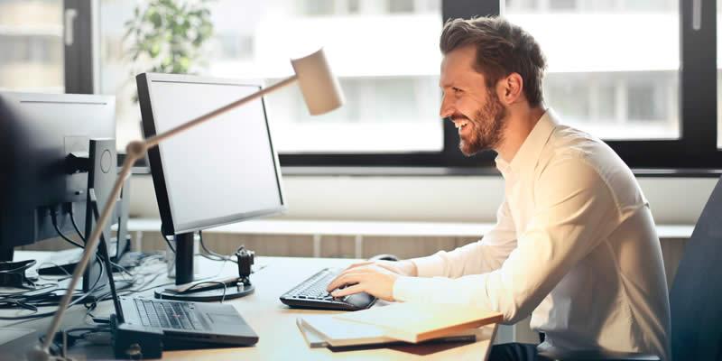 Homem em mesa iluminada usando computador