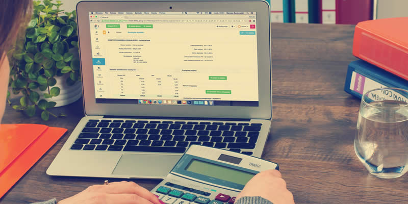 Mulher realizando operações financeiras em frente ao computador, com uma calculadora em mãos