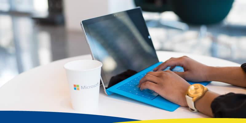 Notebook em cima de mesa, com copo ilustrado com o logotipo da Microsoft ao lado