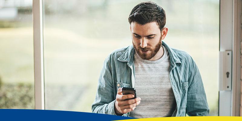 Homem, em frente a uma janela, olhando o celular