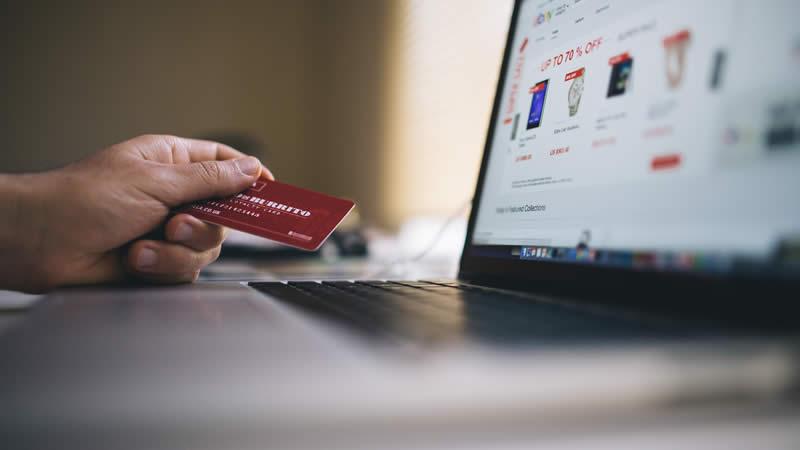 Mão segurando cartão de crédito em frente a um notebook
