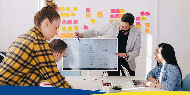 Pessoas planejando em uma mesa de escritório, com post-its ao fundo